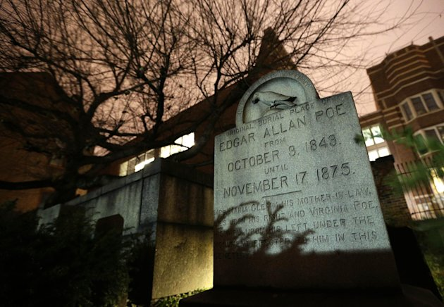 In this Jan. 15, 2013 photo, a gravestone marking Edgar Allan Poe&#39;s original grave stands in a cemetery outside Westminster Hall in Baltimore. For decades, a mysterious man known as the Poe Toaster left three roses and an unfinished bottle of cognac at Poes grave every year on the legendary writers birthday. His identity is a great modern mystery, and just as mysteriously, the tradition ended four years ago. (AP Photo/Patrick Semansky)