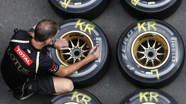 A Lotus Formula One mechanic marks tyres (Reuters)