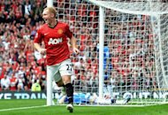 Manchester United's midfielder Paul Scholes, playing his 700th game for United, celebrates scoring the opening goal of their English Premier League football match against Wigan Athletic at Old Trafford in Manchester. Manchester United won 4-0