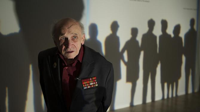 In this photo taken on Thursday, Dec. 5, 2012, artist Leonid Rabichev stands near the entrance to an exhibition at Moscow's Manezh hall on Wednesday, Russia.  The 89-year-old Rabichev was one of the artists whose works were banned by Soviet leader Nikita Khruschev after an exhibition in  the Manezh hall  in December 1962. Fifty years later, some of the banned canvases are on display again at the same Manezh hall _ at a time when critics compare Khruschev's ban to recent charges against the Pussy Riot band and artists whose paintings have angered the Kremlin and Russia's dominant Orthodox Church. (AP Photo/Alexander Zemlianichenko)