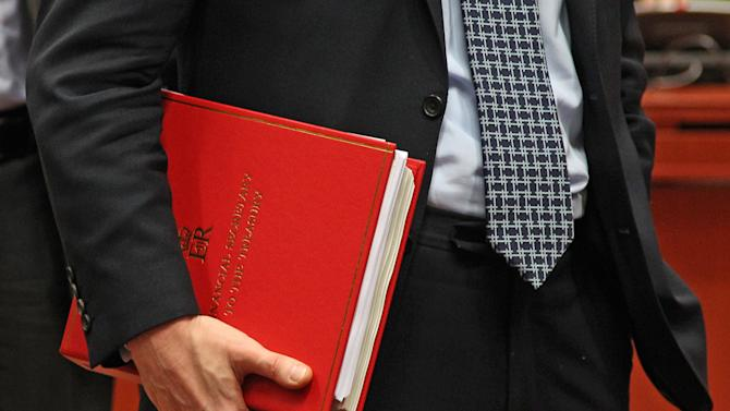 British Financial Secretary to the Treasury Greg Clark, holds his documents, during the EU finance ministers meeting, at the European Council building in Brussels, Tuesday, Dec. 4, 2012. European Union finance ministers will seek to agree Tuesday to the principles of a eurozone banking supervisor, EU diplomats said. Earlier this year, the 27 member states pledged to reach the outlines of an agreement by the end of 2012, allowing the supervisor to come into force during the course of the following year. (AP Photo/Yves Logghe)