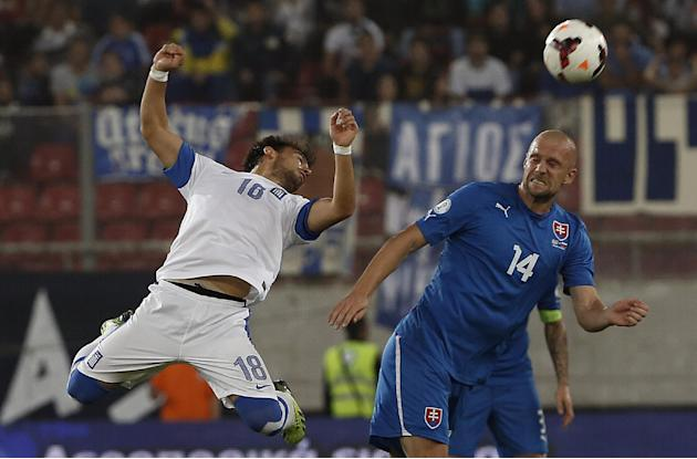 Greece's Lazaros Christodoulopoulos, left,  fights for the ball with Slovakia's Martin Jacubo  during their World Cup Group G qualifying soccer match at the Karaiskaki stadium in the port of Piraeus,