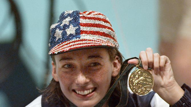 FILE - In this July 26, 1996 file photo, Olympic gold medalist Amy Van Dyken holds her medal after winning the women's 50 meter freestyle at the 1996 Summer Olympic Games in Atlanta. Van Dyken has a severed spine after an accident on her all-terrain vehicle in Arizona. A hospital spokeswoman didn't provide details Monday on the injuries. The swimmer was hurt Friday night, June 6, 2014, and told emergency workers at the scene she could not move her toes or feel anything touching her legs. (AP Photo/Lynne Sladky, File)