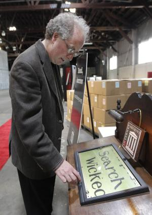 """In this July 21, 2011 photo, Brewster Kahle, digital librarian for the Internet Archive, demonstrates the zoom function while scanning a book on a touch screen at the Internet Archive's Physical Archive warehouse in Richmond, Calif.  Saving a copy of every Web page ever posted sounds like an ambitious life's work, but Khale has decided digital isn't enough. The founder of the Internet Archive wants to expand his effort to provide """"universal access to all knowledge"""" by preserving a physical copy of every book ever written. (AP Photo/Jeff Chiu)"""