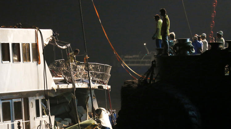 Workers look at a salvaged boat which sank previous night after colliding with a ferry near Lamma Island, off the southwestern coast of Hong Kong Island Tuesday, Oct. 2, 2012. The boat packed with revelers on a long holiday weekend sank, killing nearly 40 people and injuring dozens, authorities said. (AP Photo/Kin Cheung)