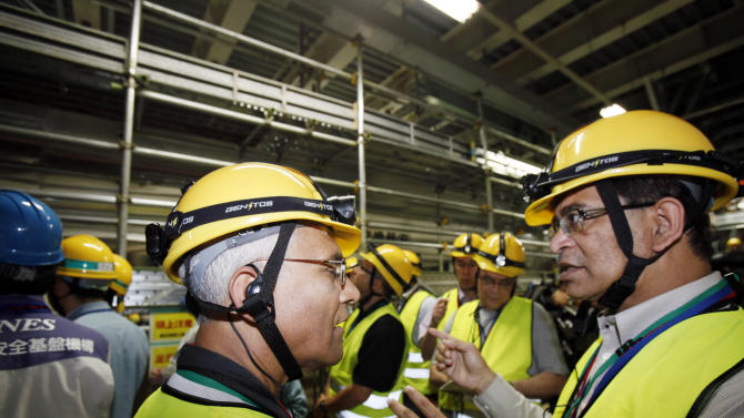 International Atomic Energy Agency group head, Sujit Samaddar, right, talks with IAEA expert Manas Kummar Chakravorty, during their inspection of the heat exchanger at the Onagawa nuclear power plant in Onagawa, Miyagi prefecture, northeastern Japan, Tuesday, July 31, 2012. The 20-member IAEA mission, first at the Onagawa nuclear power plant, about 120 kilometers (74 miles) north of Fukushima Dai-ichi nuclear plant, since the crisis, aims to find out the extent of damage at the plant from the magnitude 9.0 quake. (AP Photo/Koji Sasahara)