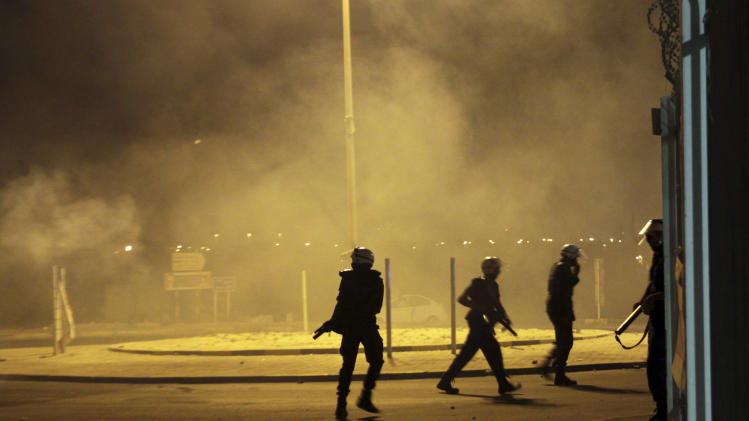 "Riot police fire tear gas and stun grenades to disperse villagers gathering near the site in Sadad, Bahrain, early Saturday, Sept. 29, 2012, where a youth was killed during an anti-government protest, allegedly by police shotgun fire. An Interior Ministry statement said a police patrol was attacked with petrol bombs and iron rods late Friday, and one person died when ""policemen defended themselves."" A witness among protesters said demonstrators were marching against the government when a policeman suddenly stepped out near the youth and shot him at close range. (AP Photo/Hasan Jamali)"