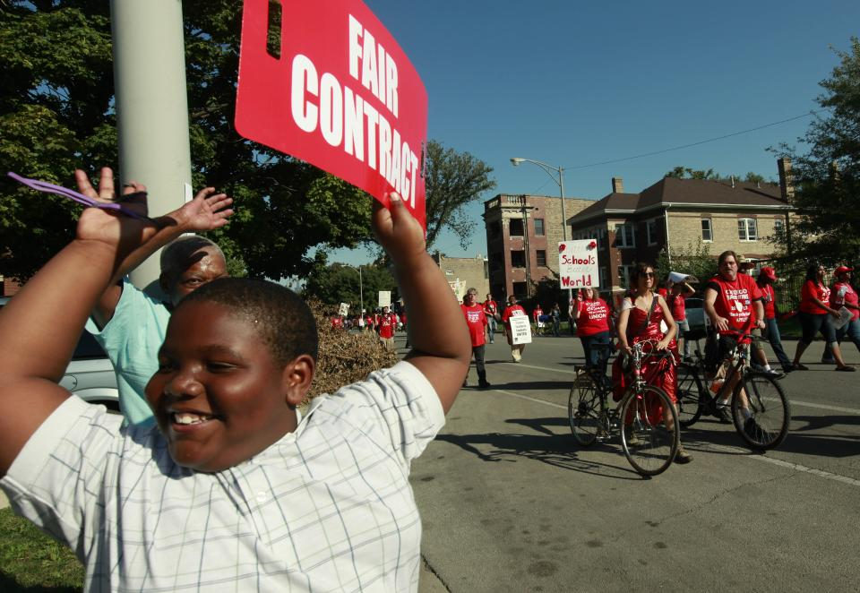 A young boy holds a placard in support of striking Chicago school teachers as they march after a rally Saturday, Sept. 15, 2012 in west Chicago. (AP Photo/Sitthixay Ditthavong)