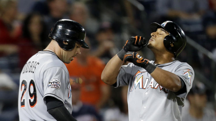 Miami Marlins' Donovan Solano, rights, looks to the sky as he crosses home plate after hitting a two-run home run to score teammate Greg Dobbs, left, in the seventh inning of a baseball game against the Atlanta Braves on Tuesday, Sept. 25, 2012, in Atlanta. (AP Photo/David Goldman)