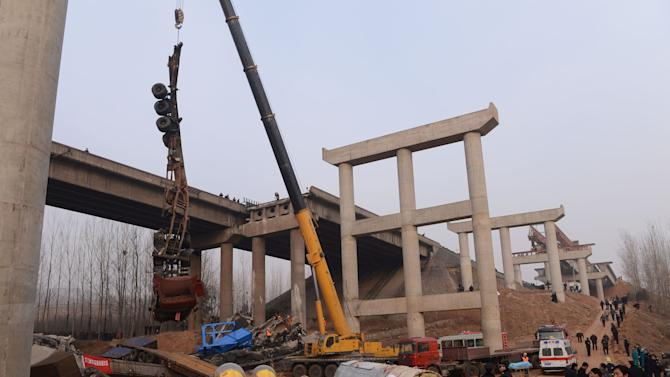 In this Feb. 1, 2013 photo provided by China's Xinhua News Agency, rescuers work at the accident locale where an 80 meter (260 foot) section of an expressway bridge collapsed due to an explosion in Mianchi County of Sanmenxia City in central China's Henan Province.  An elevated portion of highway in central China collapsed on Friday after a truck loaded with fireworks for Lunar New Year celebrations exploded, killing at least nine people and sending vehicles plummeting 30 meters (about 100 feet) to the ground. (AP Photo/Xinhua, Zhao Peng) NO SALES