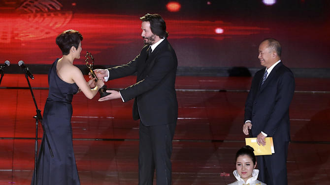 "American-Canadian actor Keanu Reeves, centre, presents the best actress award to Chinese actress Yan Bingyan, left, as Hong Kong director John Woo, right,  looks on during the award ceremony for the Beijing Film Festival in Beijing Tuesday April 23, 2013. Reeves stars in his new movie ""Man of Tai Chi,"" which also marks Reeve's directorial debut. (AP Photo) CHINA OUT"