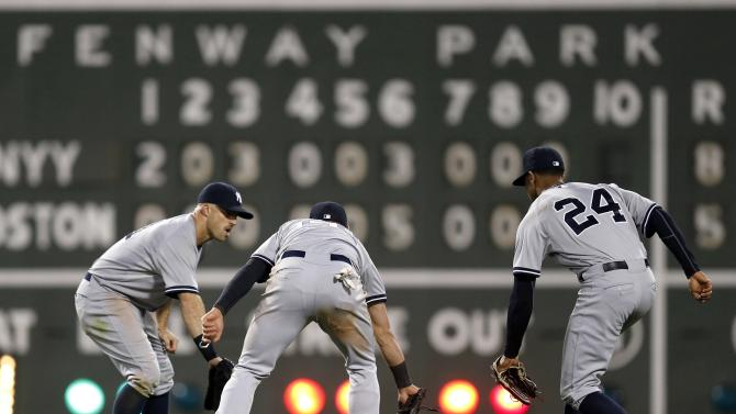 New York Yankees outfielders from left, Brett Gardner, Jacoby Ellsbury and Chris Young celebrate after defeating the Boston Red Sox 8-5 in a baseball game in Boston, Sunday, May 3, 2015. (AP Photo/Michael Dwyer)