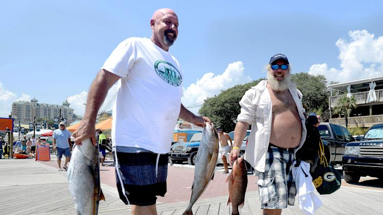 Chuck Minkowski, left, and Steve Bader, who both served in the Navy, smile as they carry their fish to the scale, Saturday, Aug. 23, 2014, after returning from a fishing trip in the Gulf of Mexico for the Emerald Coast Association of Realtors' Soldiers on the Water at the Destin Harbor in Destin, Fla. The event was created to take wounded warriors out for a fishing trip as a form of fun, therapy and thanks for their military service. (AP Photo/Northwest Florida Daily News, Nick Tomecek)