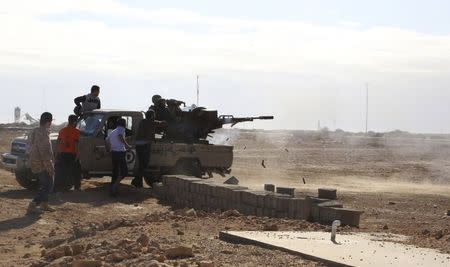 Libyan Army Forces belonging to Libya's rival government, that are part of the Libya Dawn operation to free oil ports, fire a vehicle-mounted weapon on the outskirts of Al Sidra oil port