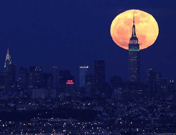 FILE - A full moon rises behind the Empire State Building in New York in this view from Eagle Rock Reservation in West Orange, N.J., in this April 6, 2012 file photo. The biggest and brightest full moon of the year arrives Saturday night May 5, 2012 as our celestial neighbor passes closer to Earth than usual. Saturday&#39;s event is a &quot;supermoon,&quot; the closest and therefore the biggest and brightest full moon of the year. At 11:34 p.m., the moon will be about 221,802 miles from Earth. That&#39;s about 15,300 miles closer than average. (AP Photo/Julio Cortez, File)