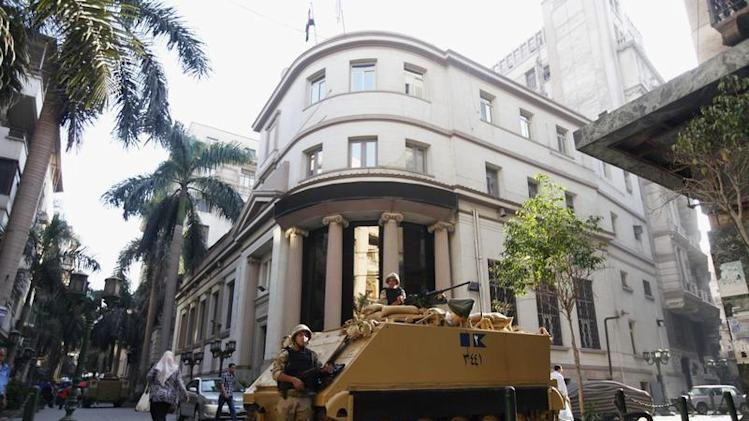 A soldier stands next to an armoured personnel carrier (APC) near the Egypt stock exchange near Tahrir Square in Cairo
