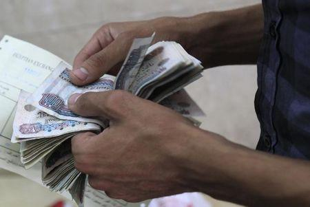 A man counts his bills at a foreign exchange office in downtown Cairo