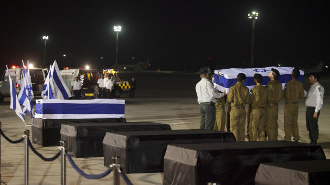 Israeli soldiers carry the coffins of people killed in a bombing in Bulgaria as the remains arrived back at an airport in Tel Aviv, Israel, Friday, July 20, 2012.  A man carried out a deadly suicide attack on a bus full of Israeli vacationers on Wednesday in the Black Sea resort town of Burgas, a popular destination for Israeli tourist. (AP Photo/Dan Balilty)