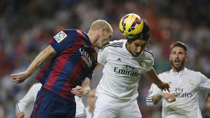 Real Madrid's Sami Khedira, centre, in action with Barcelona's Jeremy Mathieu, left, during a Spanish La Liga soccer match between Real Madrid and FC Barcelona at the Santiago Bernabeu stadium in Madrid, Spain, Saturday, Oct. 25, 2014. (AP Photo/Andres Kudacki)