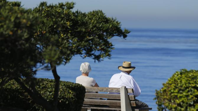 An elderly couple looks out at the ocean as they sit on a park bench in La Jolla, California