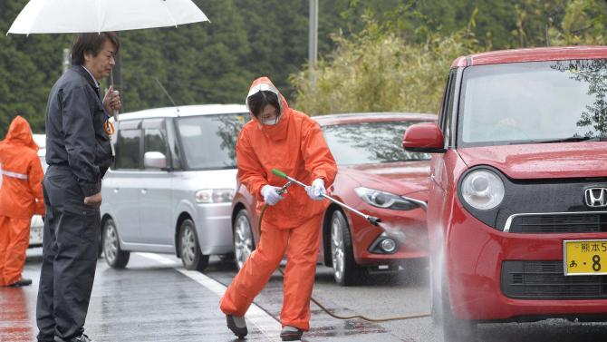 Local government employee sprays antiseptic solution on a car on a road leading to Taragi town, in Hitoyoshi, Kumamoto prefecture