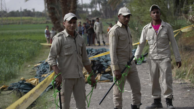 Egyptian policemen stand guard at the site of the balloon accident, in Luxor, Egypt, Tuesday, Feb. 26, 2013. A hot air balloon flying over Egypt's ancient city of Luxor caught fire and crashed into a sugar cane field on Tuesday, killing at least 19 foreign tourists in one of the world's deadliest ballooning accidents and handing a new blow to Egypt's ailing tourism industry. (AP Photo/Nasser Nasser)
