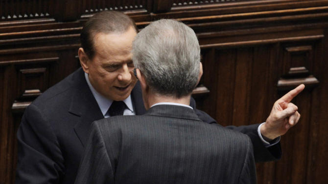 "FILE - In this  Friday, Nov. 18, 2011 file photo, Italy's former Premier Silvio Berlusconi, left, talks to Italian Premier Mario Monti, back to camera, at the lower chamber in Rome. Although Berlusconi resigned in disgrace a year ago, has been convicted of tax fraud and now faces plunging poll numbers, the media baron confirmed to reporters Saturday, Dec. 8, 2012, that he'll try for a fourth term. Berlusconi yanked support for Premier Mario Monti's technocrat government on Thursday, increasing the prospects for early elections. Monti calls the political crisis triggered by the loss of Berlusconi's support ""manageable"" and says his government has rescued Italy from financial disaster. (AP Photo/Gregorio Borgia, File)"