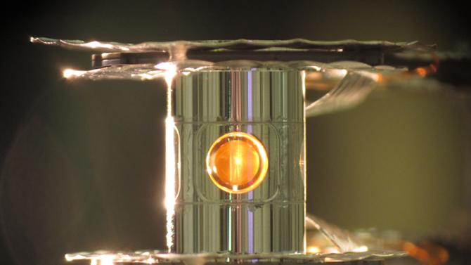 This undated image provided by the Lawrence Livermore National Laboratory shows a deuterium and tritium capsule, sphere in window at center, inside a cylindrical hohlraum container about 0.4 inches tall. In research reported Wednesday, Feb. 12, 2014 by the journal Nature, scientists say they've taken a key step toward harnessing nuclear fusion as a new way to generate power, an idea that has been pursued for decades. In tests, 192 laser beams briefly fired into the small gold cylinder which held the two kinds of hydrogen. The energy from the lasers kicked off a process that compressed the ball by an amount akin to squeezing a basketball down to the size of a pea, said Debbie Callahan, an author of the paper. That created the extremely high pressure and temperatures needed to get the hydrogen atoms to fuse. (AP Photo/Lawrence Livermore National Laboratory, Eddie Dewald)