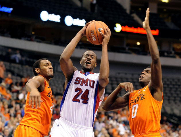 SMU forward Robert Nyakundi (24) drives to the basket between Oklahoma State guard Brian Williams (4) and forward Jean-Paul Olukemi (0)in the second half of an NCAA college basketball game in Dallas,