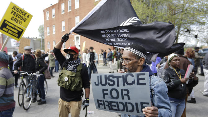 Protestors gather outside the Baltimore Police Department's Western District police station before a match for Freddie Gray, Saturday, April 25, 2015, in Baltimore. Gray died from spinal injuries about a week after he was arrested and transported in a police van. (AP Photo/Patrick Semansky)