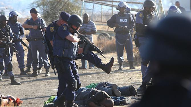 Police surround the bodies of striking miners after opening fire on a crowd  at the Lonmin Platinum Mine near Rustenburg, South Africa, Thursday, Aug. 16, 2012. An unknown number of people have been killed and injured. Police moved in on workers who gathered on a rocky outcropping near the Lonmin late afternoon, firing unknown ammunition.  (AP Photo) SOUTH AFRICA OUT