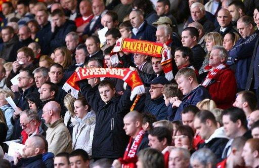 Liverpool supporters hold scarves during a singing of 'You'll Never Walk Alone' at Anfield in 2008