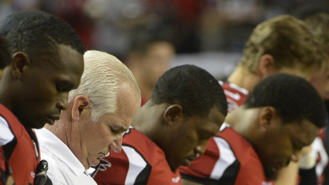 Atlanta Falcons head coach Mike Smith, second from left, and players close their eyes during during a moment of silence for the victims of the Sandy Hook Elementary School shootings before an NFL football game against the New York Giants, Sunday, Dec. 16, 2012, in Atlanta. A gunman walked into the school in Newtown, Conn., Friday and opened fire, killing 26 people, including 20 children. (AP Photo/Rich Addicks)