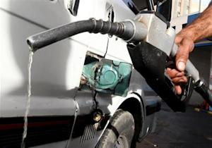 A worker fills the tank of a car at a petrol station in Cairo