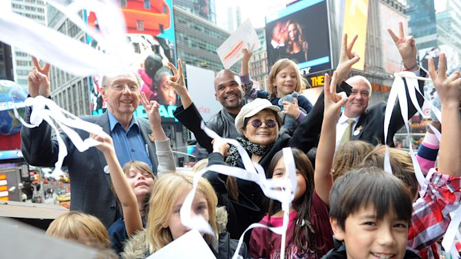 """IMAGE DISTRIBUTED FOR HARD ROCK - Yoko Ono Lennon, center, joined by Hard Rock International President & CEO Hamish Dodds, right, WhyHunger Founder Bill Ayres, left, and Darryl  """"DMC"""" McDaniels, second left, and children from a local WhyHunger beneficiary attend the launch of Hard Rock's fifth annual IMAGINE THERE'S NO HUNGER campaign, Monday, Nov. 19, 2012, in New York's Times Square.  Proceeds from the campaign benefit WhyHunger and its grassroots partners combating childhood hunger and poverty worldwide. Diane Bondareff/Invision for Hard Rock/AP Images)"""