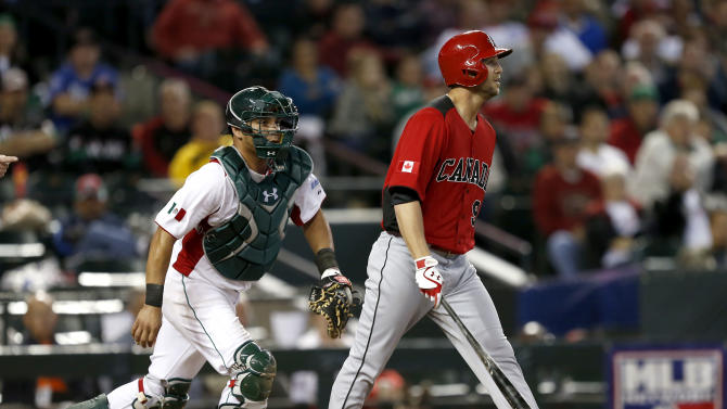 Canada's Rene Tosoni, right, walks to the mound after being hit by a pitch as Mexico's Humberto Cota pursues during the ninth inning of a World Baseball Classic game on Saturday, March 9, 2013, in Phoenix. Both benches cleared after Tosoni was hit. Canada won 10-3. (AP Photo/Matt York)