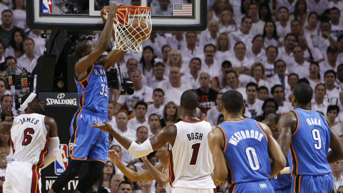 Oklahoma City Thunder small forward Kevin Durant (35) dunks as Miami Heat small forward LeBron James (6) defends during the first half at Game 5 of the NBA finals basketball series, Thursday, June 21, 2012, in Miami. (AP Photo/Lynne Sladky)