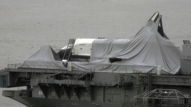 The space shuttle Enterprise is draped with cloth that had protected it before Superstorm Sandy passed though, leaving the spacecraft shrouded on the deck of  the Intrepid Sea, Air & Space Museum, at its dock on the Hudson River in New York, Tuesday, Oct, 30, 2012. Sandy, the storm which was downgraded from a hurricane just before making landfall, caused multiple fatalities, halted mass transit and cut power to more than 6 million homes and businesses. (AP Photo/Peter Morgan)