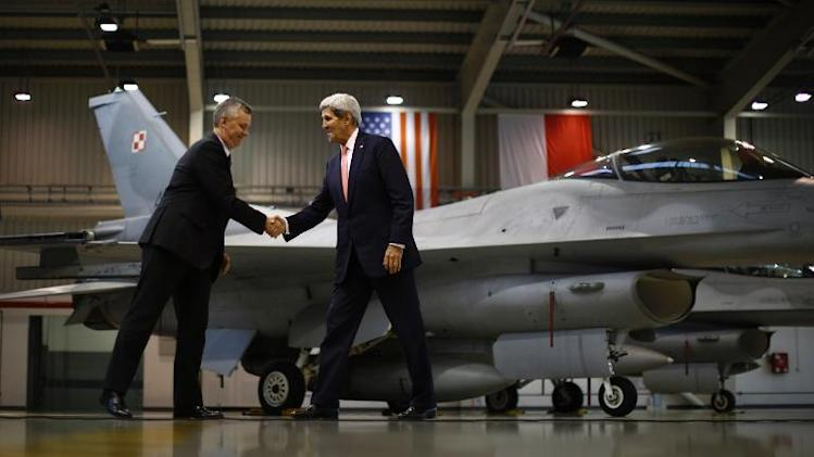 US Secretary of State John Kerry (R) shakes hands with Poland's Defence Minister Tomasz Siemoniak in front of an F-16 aircraft at the Lask Air Force Base, on November 5, 2013
