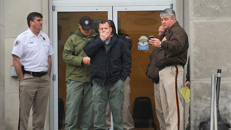 Law enforcement officers wait at the entrance to the Jackson Police Department Thursday, April, 4, 2013, after police say a murder suspect fatally shot detective Eric Smith inside the headquarters. The suspect is also dead. (AP Photo/The Clarion-Ledger, Greg Jenson)