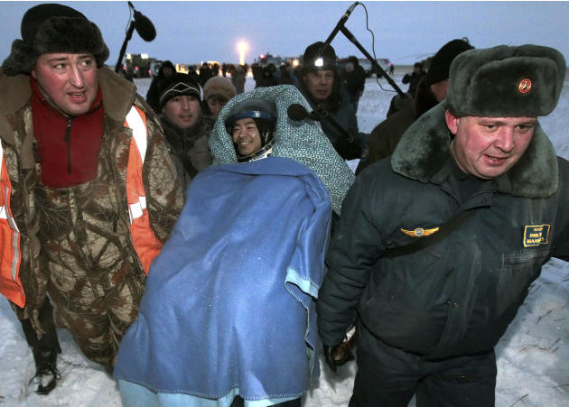 Members of the ground rescue team carry International Space Station crew member Aki Hoshide, of Japan, center, shortly after landing near the town of Arkalyk, Kazakhstan, on Monday, Nov. 19, 2012. Hos
