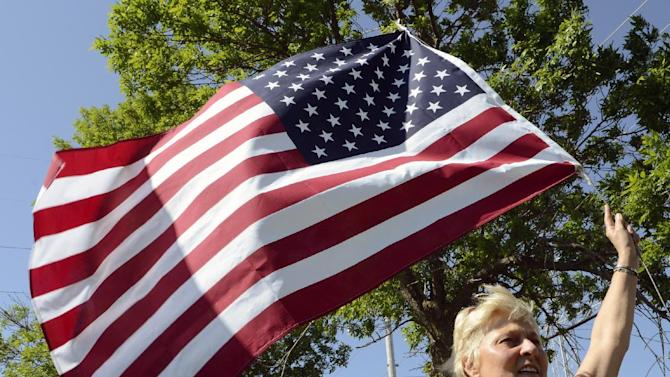 Sandy Weir of Arlington Heights, Ill. waves a U.S. flag during speeches at a rally held by the Racine Tea Party PAC in Gorney Park in Caledonia, Wis. near Racine on Saturday, June 2, 2012. The rally was held in opposition to the Tuesday, June 5, 2012 recall election in which Democratic opponents are running against incumbents Gov. Scott Walker, Lt. Gov. Rebecca Kleefisch, and State Sen. Van Wanggaard of Racine. At least 2,000 people attended the event. (AP Photo/Mark Hertzberg)