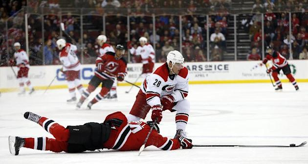 New Jersey Devils defenseman Jon Merrill, bottom, falls to the ice while challenging Carolina Hurricanes right wing Alexander Semin, of Russia, for the puck during the first period of an NHL hockey ga