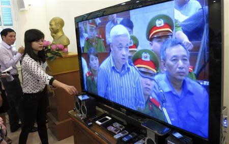 A journalist places a recording device next to a TV screen showing live images from a courtroom in Hanoi