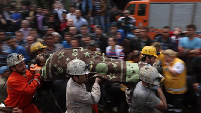 Rescue workers carry the dead body of a miner outside the coal mine in Soma, Turkey, Wednesday, May 14, 2014. An explosion and fire at the coal mine killed at least 232 workers, authorities said, in one of the worst mining disasters in Turkish history. Turkey's Energy Minister Taner Yildiz said 787 people were inside the coal mine at the time of the accident. (AP Photo/Emrah Gurel)