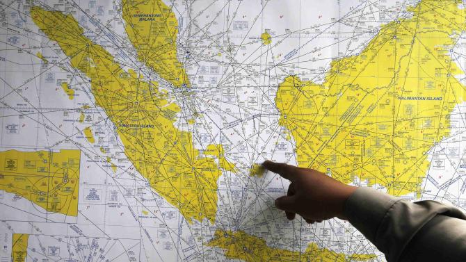 Indonesian policeman points at a map of Indonesia at a crisis centre in Juanda International Airport, Surabaya