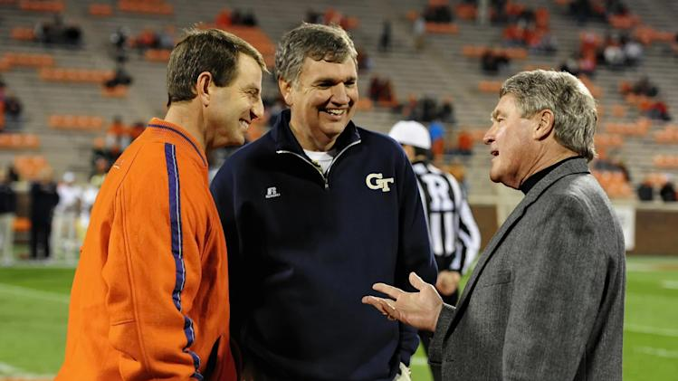 Clemson head coach Dabo Swinney, left, and Georgia Tech head coach Paul Johnson, center, talk with ACC Commissioner John Swofford before an NCAA college football game on Thursday, Nov. 14, 2013, in Clemson, S.C