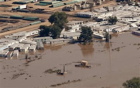 An oil storage tank on a well pad lies toppled near portable buildings surrounded with flood waters in Weld County, Colorado
