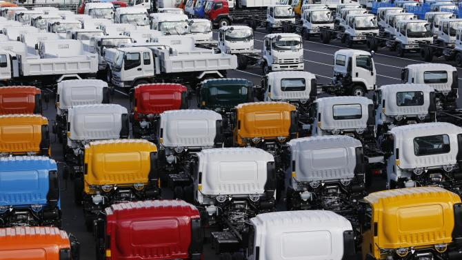 In this Dec. 20, 2012 photo, trucks for export park at a port in Yokohama, west of Tokyo. A steady decline in the yen is proving a godsend for exporters such as Toyota and has won solid support from Japan's main trading partners, who are betting the impact on their own currencies will be offset by gains from a recovery in the world's third-largest economy. (AP Photo/Koji Sasahara)