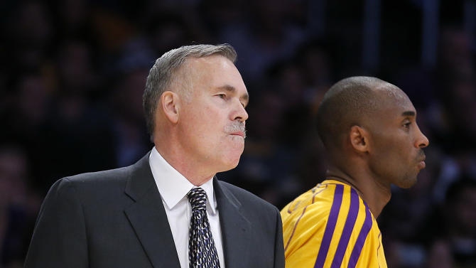 Los Angeles Lakers' Kobe Bryant, right, walks past head coach Mike D'Antoni in the second half of an NBA basketball game against the Brooklyn Nets in Los Angeles, Tuesday, Nov. 20, 2012. The Lakers won 95-90. (AP Photo/Jae C. Hong)